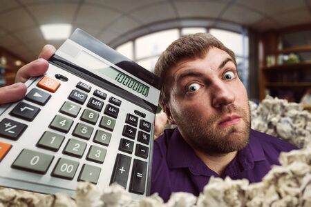 enumeration: Surprised accountant holds calculator with a big total