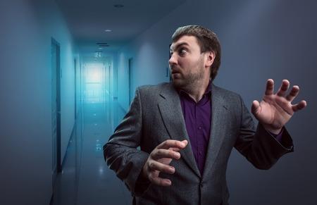 Gevreesde zakenman die in de donkere gang loopt