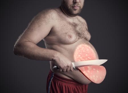 Gros homme coupe une grosse tranche de saucisson de son ventre plus gris