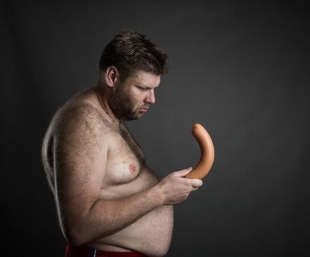 pene: Vista lateral del hombre gordo mirando la salchicha en la mano sobre gris. Problema Potencia