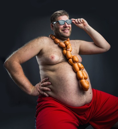 and fat: Happy man sitting with heap of sausages on his head and with sausages round his neck Stock Photo