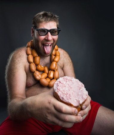 wurst: Ugly hungry man with sausages round his neck eats a big wurst over grey