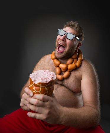 wurst: Hungry man with sausages round his neck eats a big wurst over grey