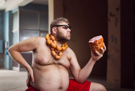hombre con barba: Hombre gordo con salchichas al cuello mira a una gran salchicha en la sala de Foto de archivo
