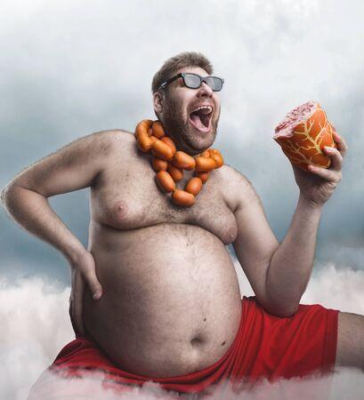 hombre con barba: Hombre enojado en copas con salchichas redondas del cuello tiene una gran salchicha en la mano y grita en la neblina Foto de archivo