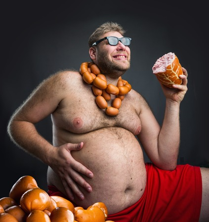 wurst: Happy man in glasses with sausages round his neck holds a big wurst in his hand over grey