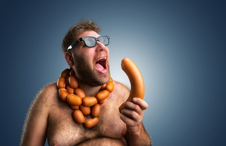 wurst: Hungry man with sausages round his neck eats a big wurst over blue