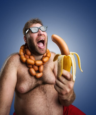 wurst: Mad man in glasses with sausages round his neck holds a big wurst in bananas peel over blue