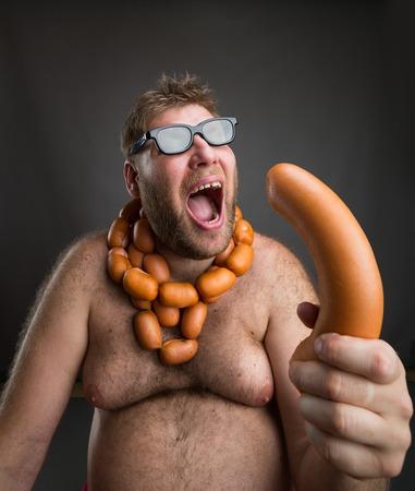 hombre con barba: Hombre gordo hambriento con salchichas al cuello come una gran salchicha sobre gris Foto de archivo