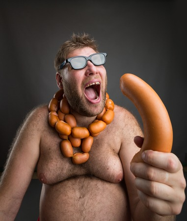 beard man: Hungry fat man with sausages round his neck eats a big wurst over grey Stock Photo