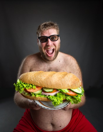 hungry: Fat happy man in glasses with sandwich Stock Photo