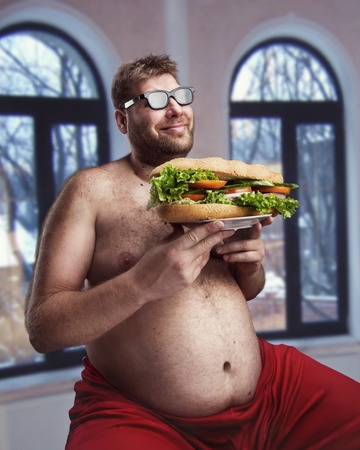 Fat happy man in glasses with sandwich sits in the room Stock Photo