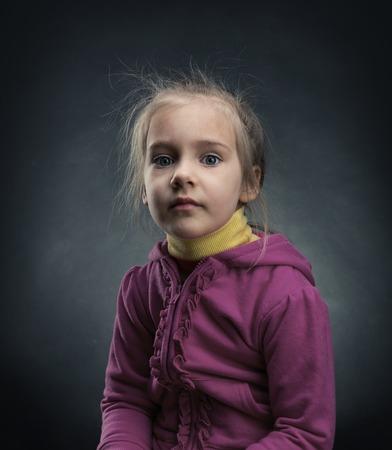 depressed girl: Sad little girl in pink jacket over dark