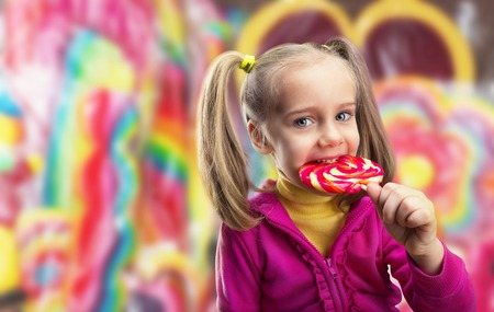 Happy little girl eating lollipop over multicolored