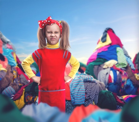 untidy: Little girl with her hands on hips stands among heaps of clothes Stock Photo