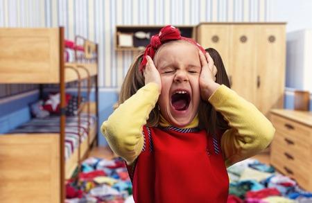 boca cerrada: Niña que grita en casa con sus oídos cubiertos por las manos