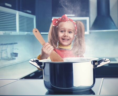 playing with spoon: Funny little girl cooking in kitchen