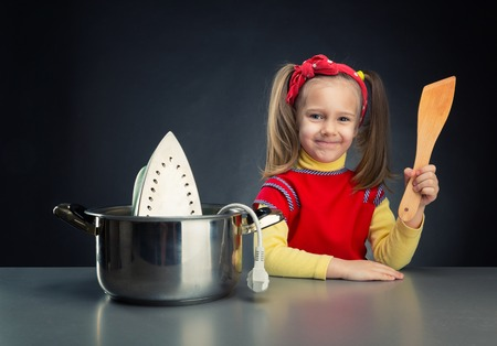 disaster: Cute smiling little girl cooking an iron in the pot