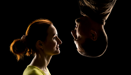 face side: Side view of womans face and mans face upside down over black Stock Photo