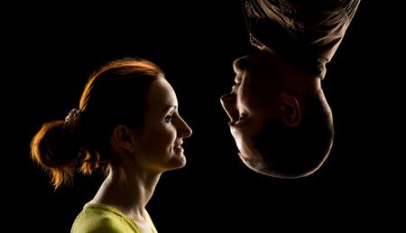 silueta humana: Vista lateral de la cara de la mujer y la cara del hombre boca abajo sobre negro