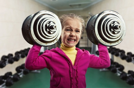 heavy weight: Little girl holding two hard dumb-bells in the gym