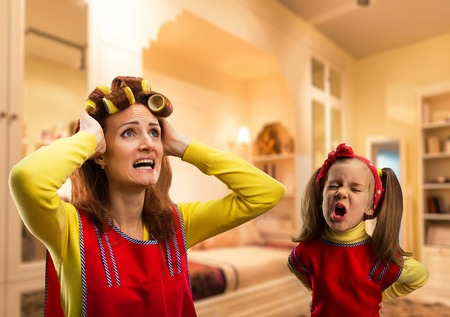 crying: Angry little girl bawling at her mother at home Stock Photo