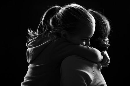 fille triste: Image noir et blanc d'une petite fille embrassant sa mère Banque d'images