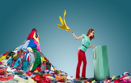 'young things': Young woman gets clothes from shopping bag and flings it behind herself over blue Stock Photo
