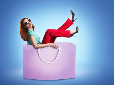 Happy smiling woman lying in the shopping bag over blue