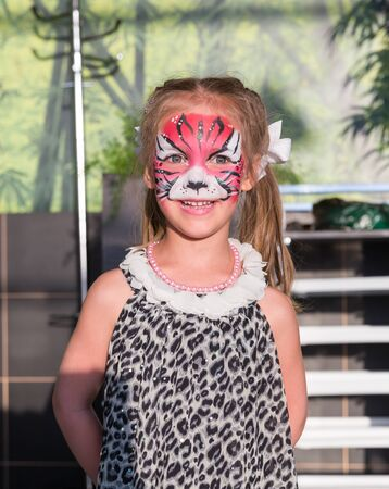 facial painting: Little girl stands with face painted as a cat