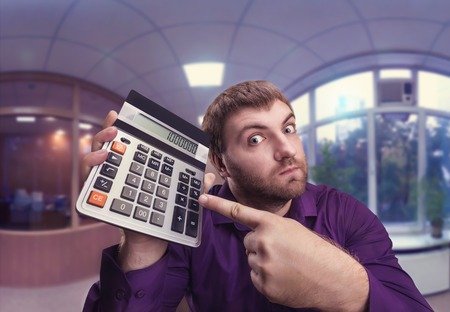enumeration: Accountant points to a calculator with a big total