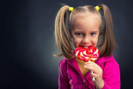 niña comiendo: Happy little girl eating lollipop over dark background
