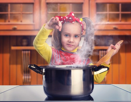 pan: Cute little girl cooking in home interior