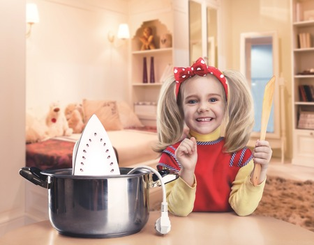 girl home: Cute smiling little girl cooking iron in the pot at home