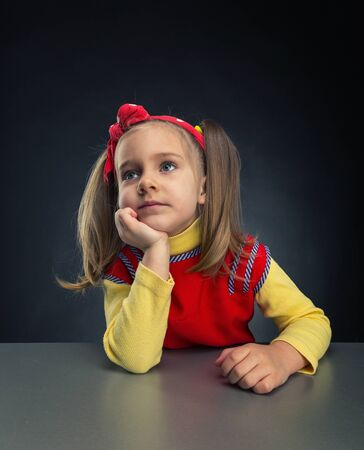 hand on the chin: Cute little girl thinks with her hand under chin Stock Photo