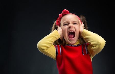 ojos llorando: La niña está gritando con sus oídos cubiertos por las manos