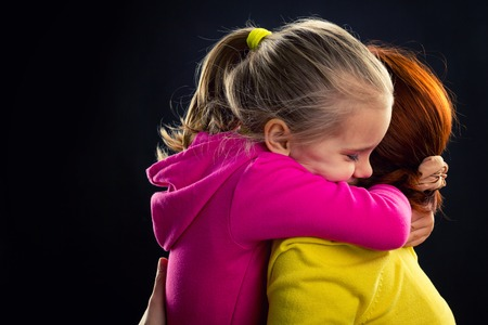 Little girl hugging her mother smiling over grey background