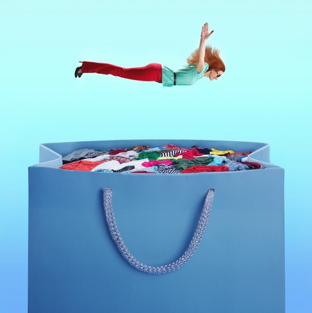 Woman flying to the heap of clothes in the shopping bag over blue