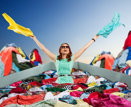 stuff: Young happy woman in sunglasses sits in the shopping bag among a big heap of clothes flinging things out