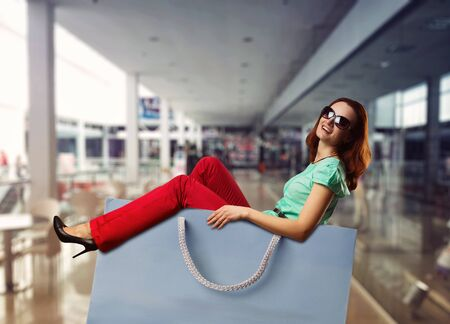 shopping trip: Happy smiling woman lying in the shopping bag in the shopping mall Stock Photo