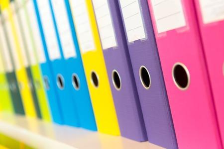 folder: Carpetas coloridas de pie en la plataforma en la oficina
