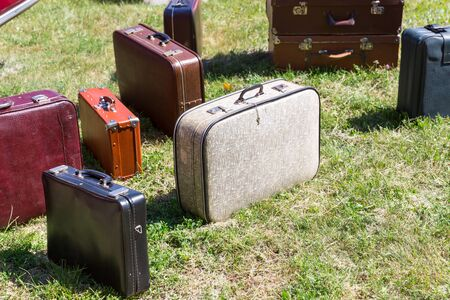 emigration: Many old suitcases standing on the grass Stock Photo
