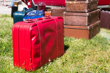 emigration: A lot of old suitcases stand on the grass Stock Photo