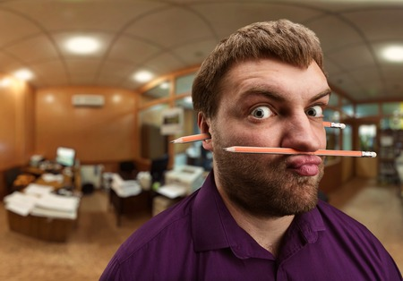 holding nose: Strange bearded man holds pencil with his nose and lips and one more pencil in his ears
