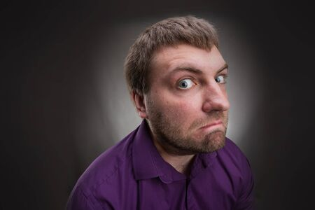 mistrust: Frustrated inquisitive man over grey background Stock Photo