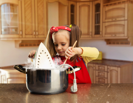 disaster: Cute smiling little girl cooking an iron in the pot at home