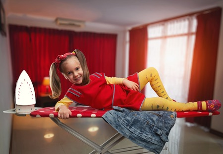 Steam iron: Happy little girl lying on the ironing-board smiling