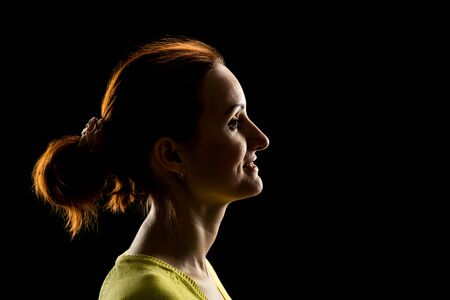 profile face: Side view of womans face over black