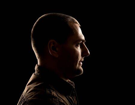 silueta masculina: Vista lateral de la cara del hombre boca abajo sobre negro Foto de archivo