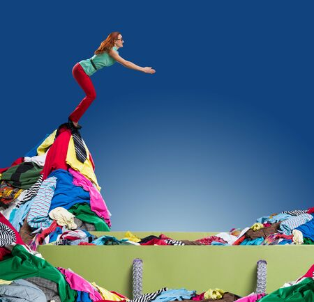 happy shopping: Woman diving to the heap of clothes in the shopping bag